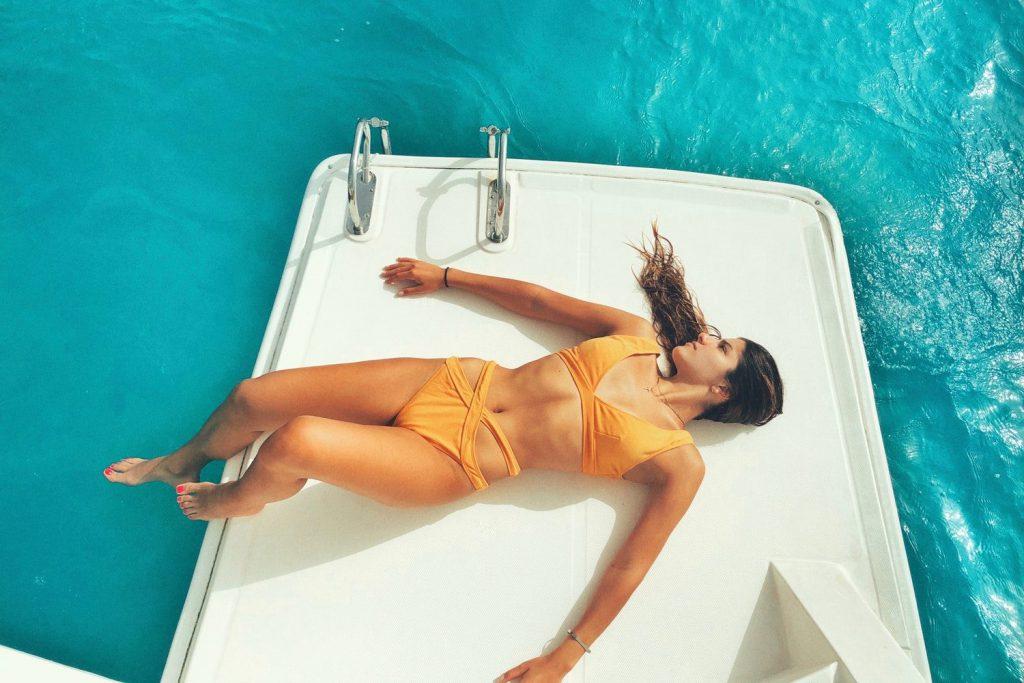Orange Bikini Woman Sunbathing on White Boat Deck